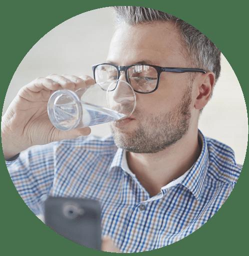 Jeune homme buvant une eau pure